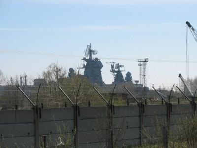 Тяжелый атомный ракетный крейсер Адмирал Ушаков выглядывает из-за забора.