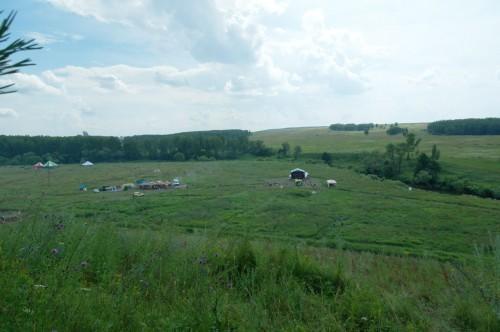 Мы на горе, под нами одна из сцен и пункты питания, а за рекой нужное нам поле.